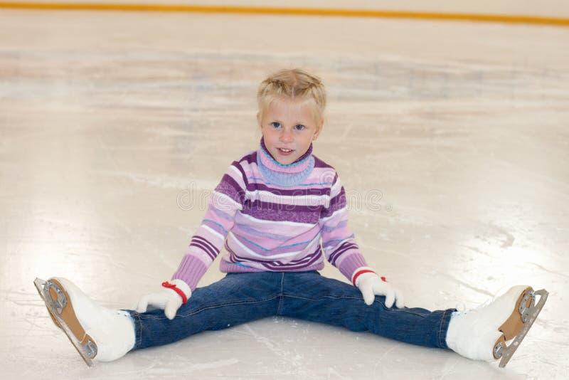 Patinagem de gelo A menina que senta-se no gelo na patinagem no gelo imagens de stock royalty free