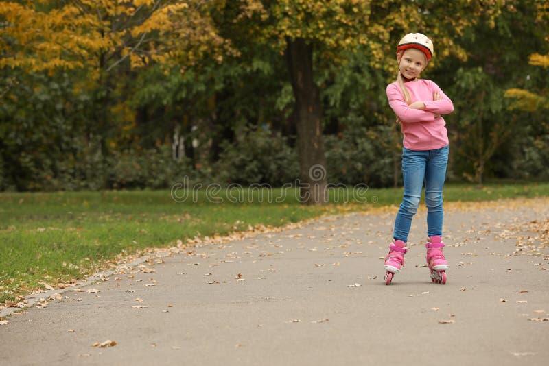 Patinagem de rolo bonito da menina no parque do outono imagens de stock