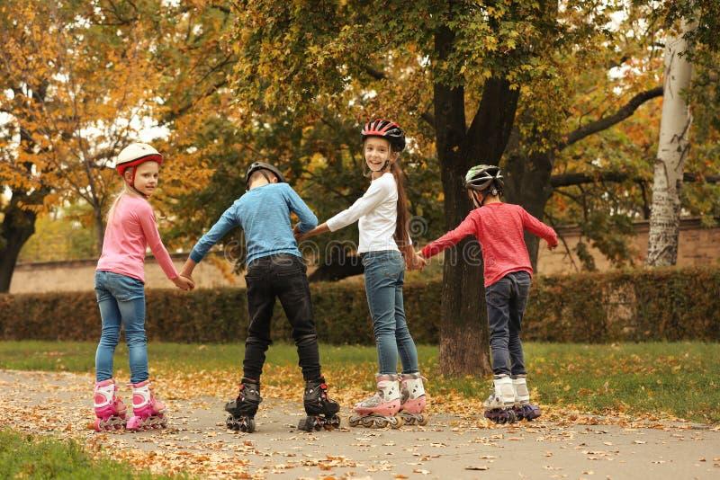 Patinagem de rolo bonito das crianças no parque fotografia de stock royalty free