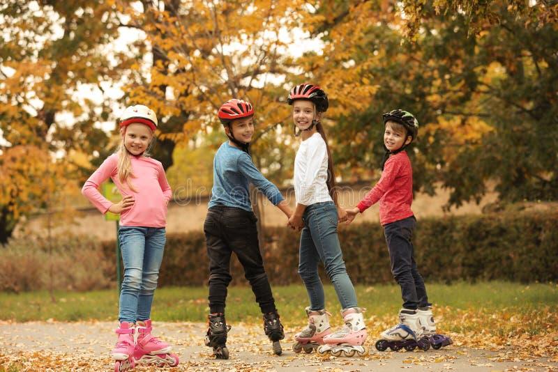 Patinagem de rolo bonito das crianças no parque imagem de stock royalty free