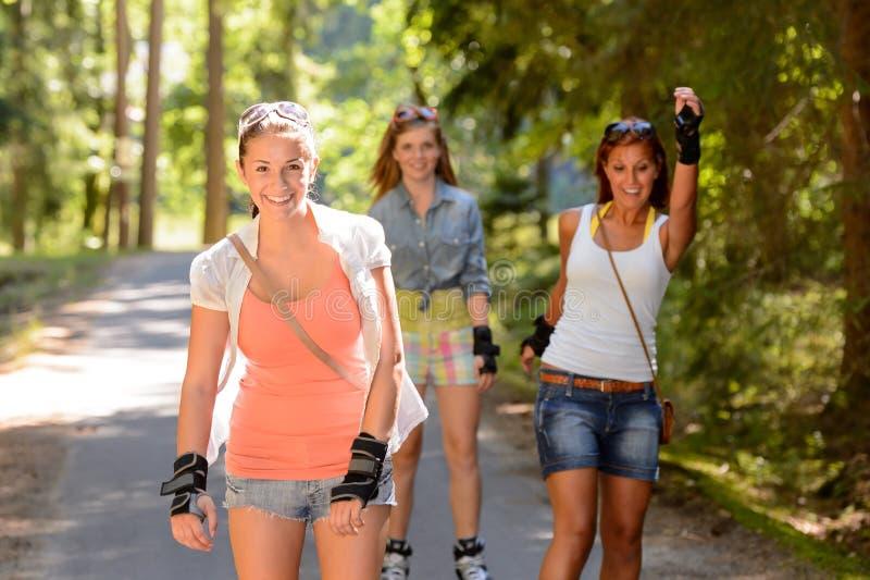 Patinagem de rolo de três amigos das mulheres fora foto de stock royalty free