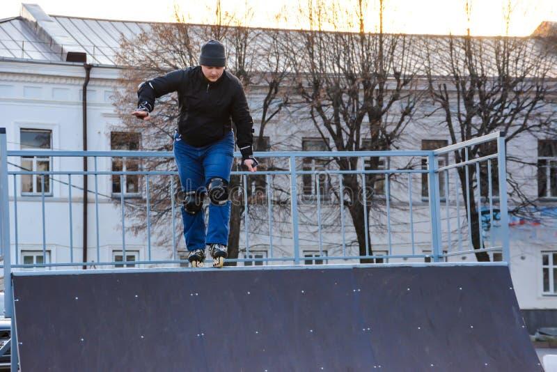 Patinagem de rolo do homem da atividade de lazer na central da cidade no por do sol Inverno foto de stock royalty free