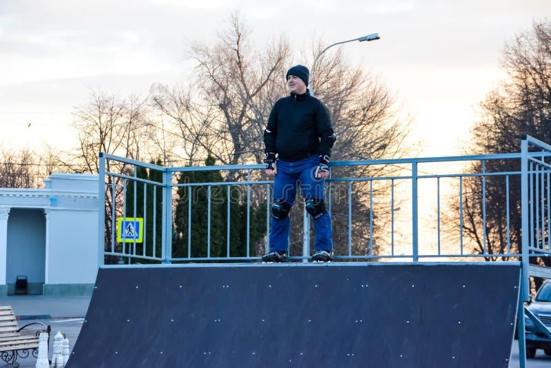 Patinagem de rolo do homem da atividade de lazer na central da cidade no por do sol Inverno fotografia de stock royalty free