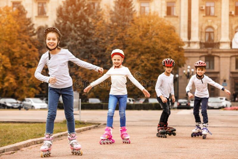 Patinagem de rolo feliz das crianças na rua imagens de stock royalty free