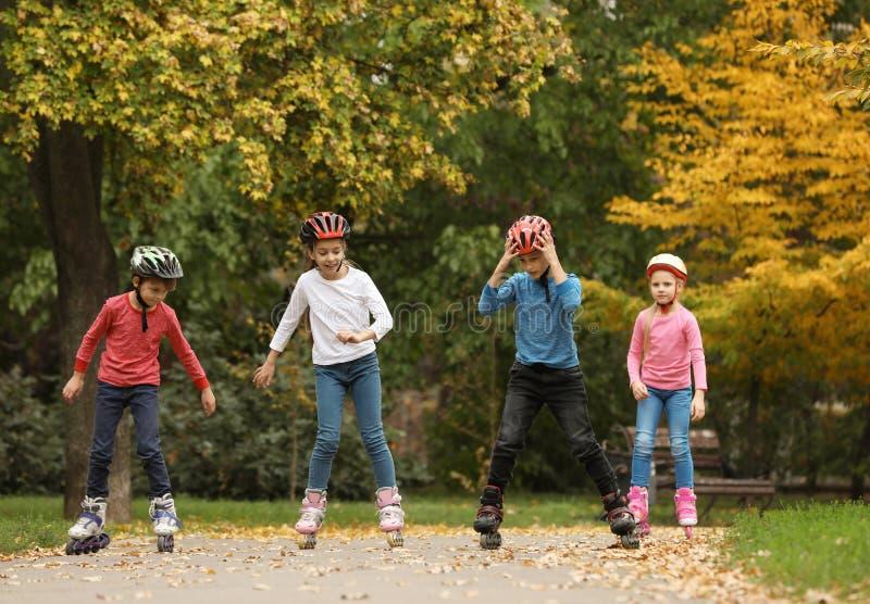 Patinagem de rolo feliz das crianças no parque imagens de stock