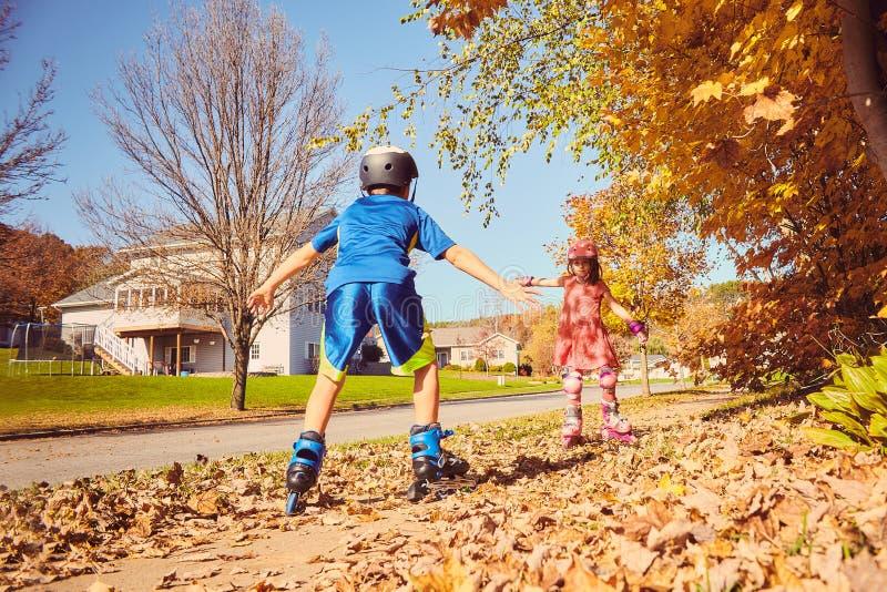 Patinagem de rolo feliz das crianças no parque do outono imagem de stock