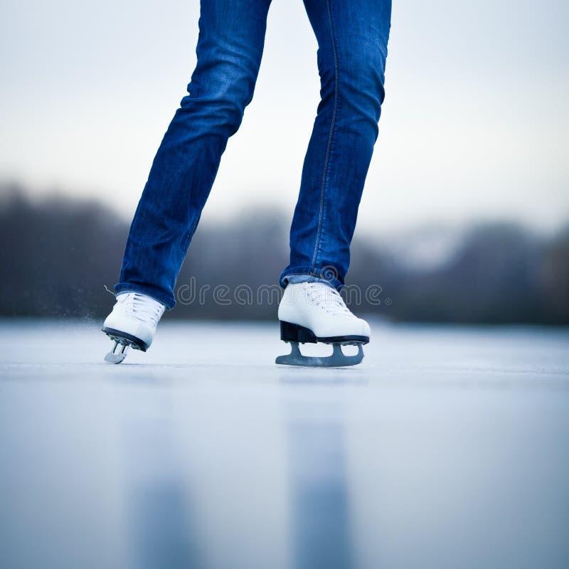 Patinagem no gelo da jovem mulher fora em uma lagoa foto de stock