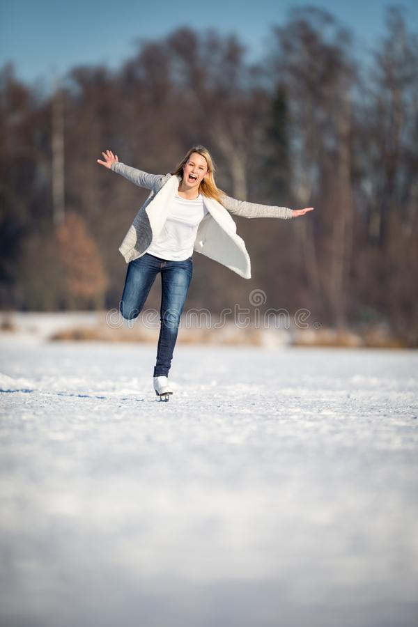 Patinagem no gelo da jovem mulher fora em uma lagoa em um inverno de congelação imagem de stock royalty free
