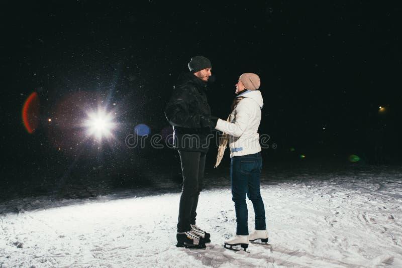 Patinagem no gelo dos pares fora em uma noite da lagoa imagem de stock royalty free