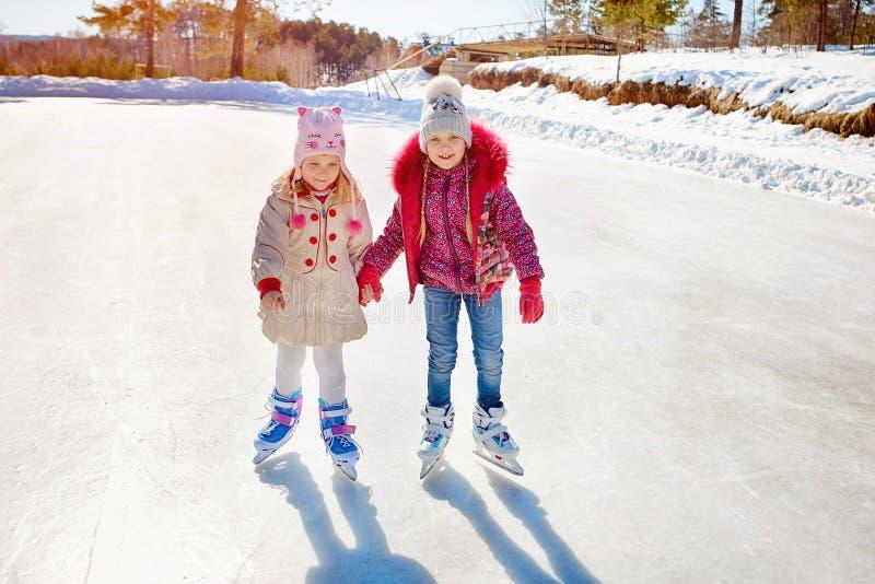 Patinagem no gelo feliz das crianças em uma pista de gelo fora esporte e um estilo de vida saudável Crianças engraçadas, são irmã imagens de stock royalty free