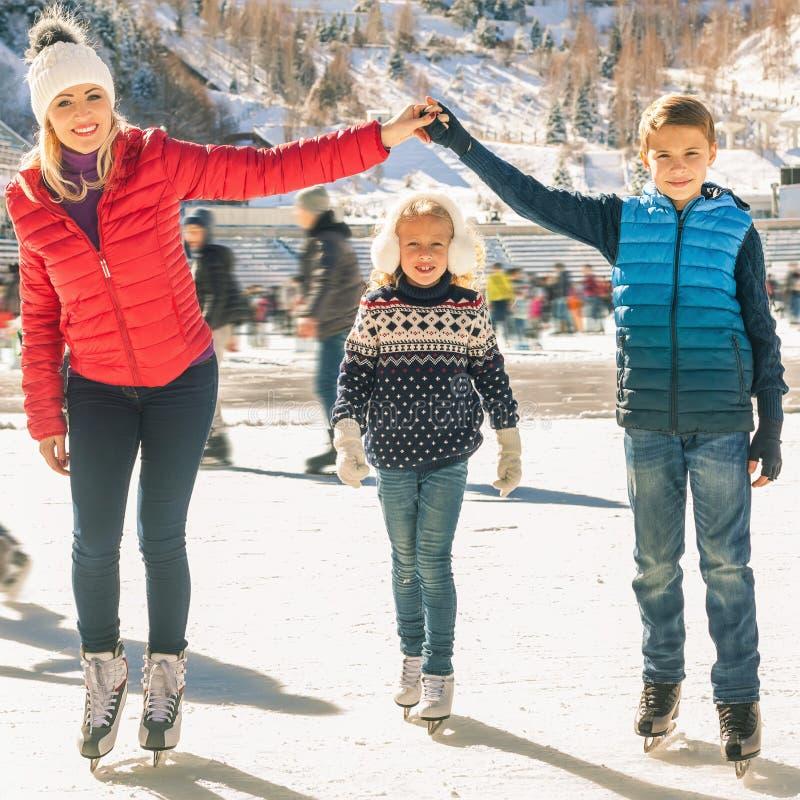 Patinaje de hielo al aire libre de la familia feliz en la pista Actividades del invierno fotografía de archivo