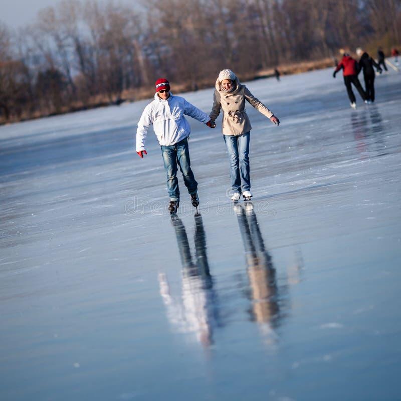 Patinaje de hielo de los pares al aire libre en una charca imagenes de archivo