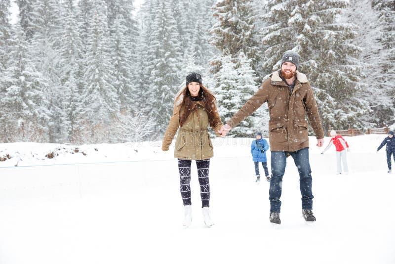 Patinaje de hielo feliz de los pares al aire libre imagen de archivo libre de regalías