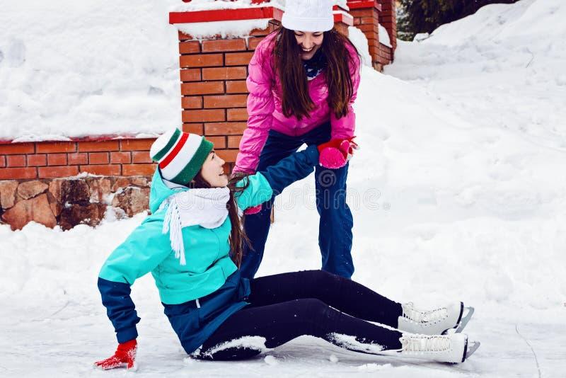 Patinaje de hielo feliz de la chica joven dos en parque del invierno Ayuda a otro para subir después de una caída fotos de archivo libres de regalías