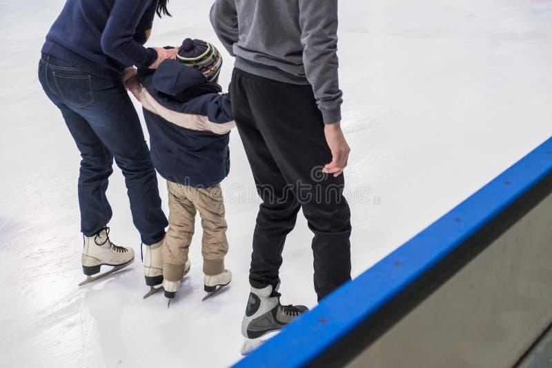 Patinaje de hielo interior de la familia feliz en la pista Invierno imagen de archivo libre de regalías