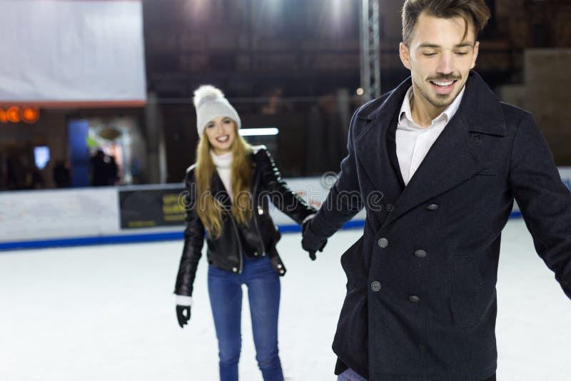 Patinaje de hielo joven hermoso de los pares en pista al aire libre fotos de archivo libres de regalías