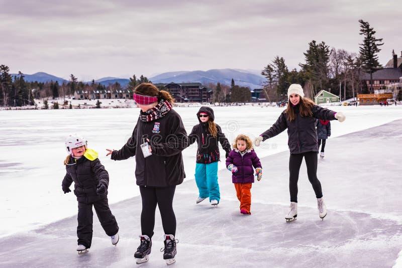 Patinaje de hielo de las muchachas en el lago mirror imagen de archivo