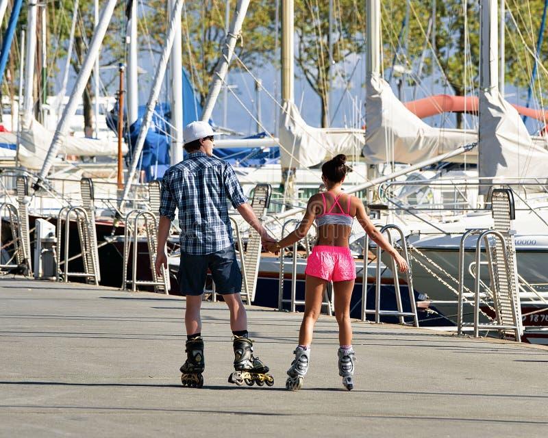 Patinaje sobre ruedas joven de los pares en el terraplén de Marina Lausanne fotos de archivo