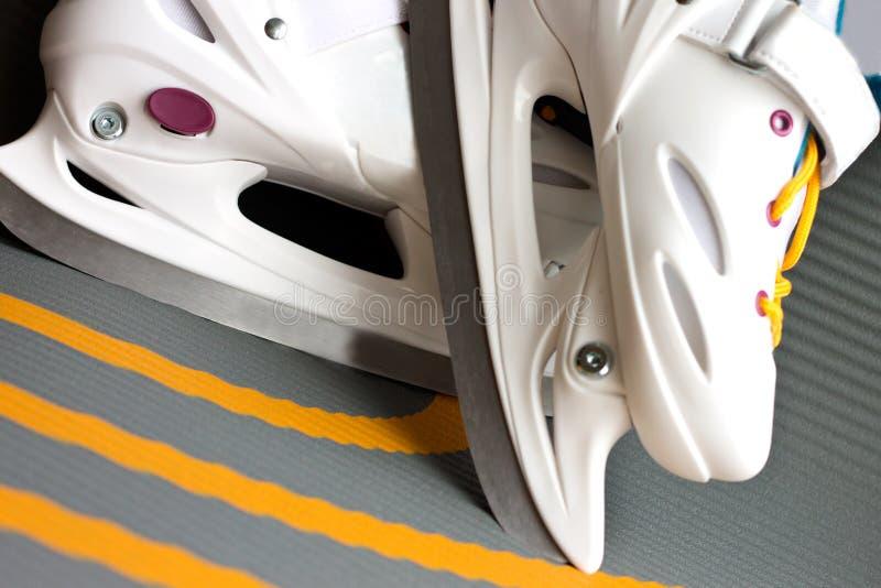 Patines de desplazamiento blancos para las muchachas que patinan en el hielo imagen de archivo libre de regalías
