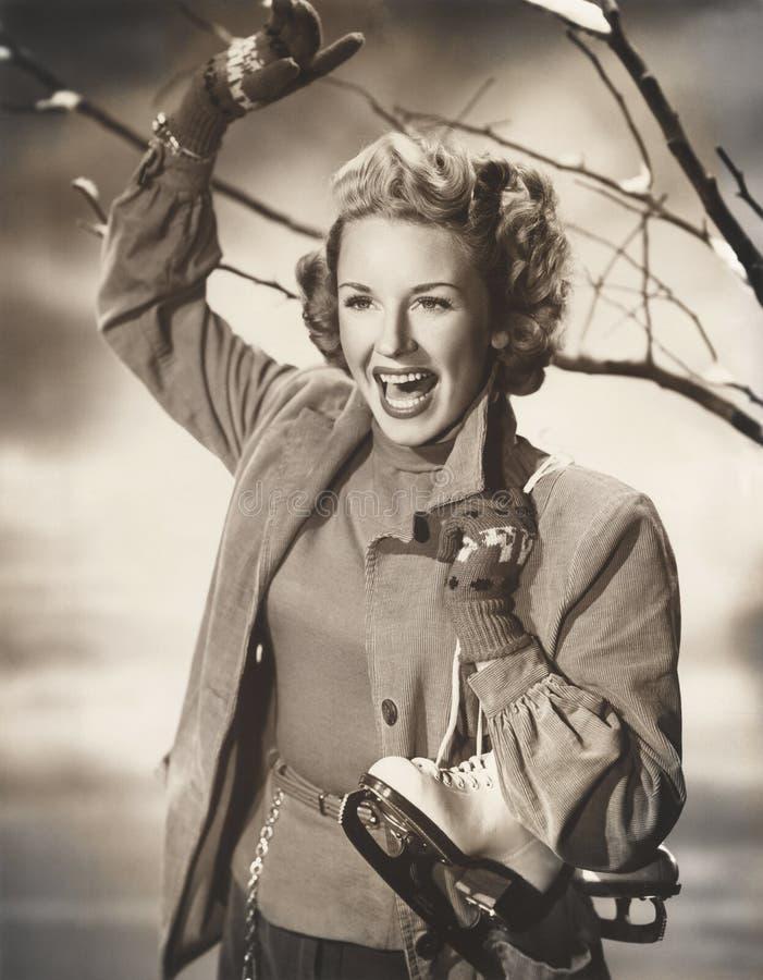 Patines de hielo de la mujer que llevan feliz imagenes de archivo