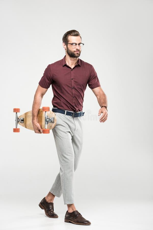 patineur élégant élégant marchant avec le longboard, photo stock
