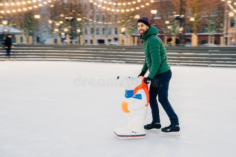 Patineur masculin heureux étant sur l'anneau de patinage, aide de patin d'utilisations comme tri image libre de droits
