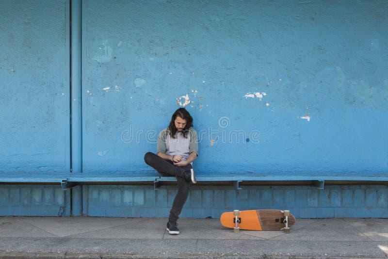 Patineur s'asseyant sur le fond bleu avec une planche à roulettes orange près de lui photos stock