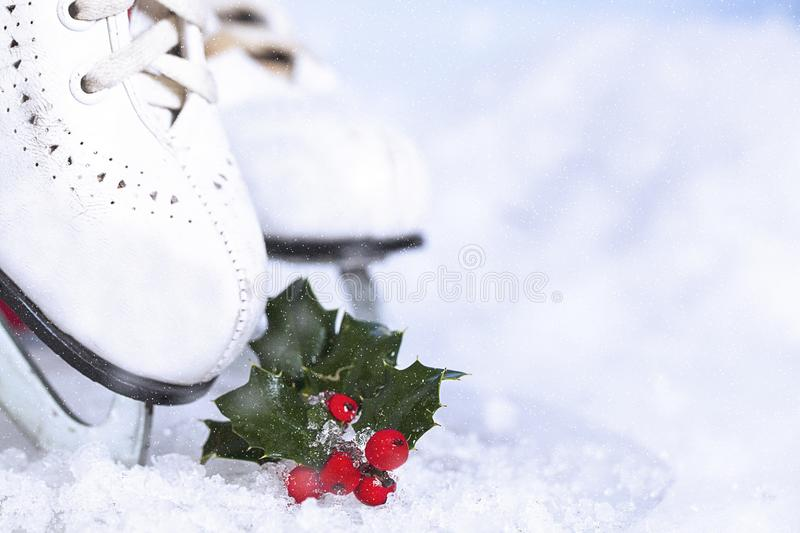 Patins blancs sur glace stoppés sur glace avec Holly photographie stock