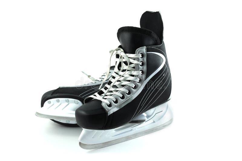 Patins d'hockey sur un fond blanc photographie stock