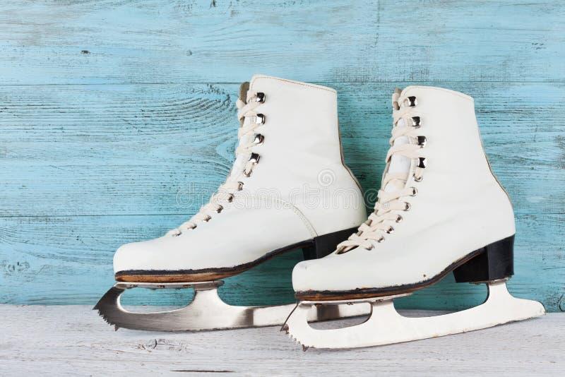 Patins de gelo do vintage para a patinagem artística no fundo de turquesa foto de stock royalty free