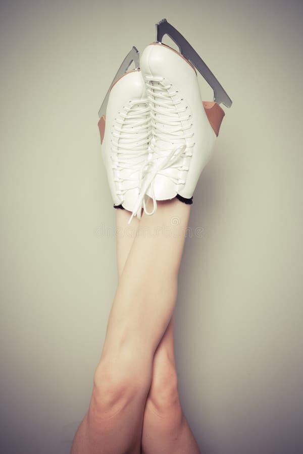 Patins de gelo vestindo da mulher contra uma parede imagens de stock