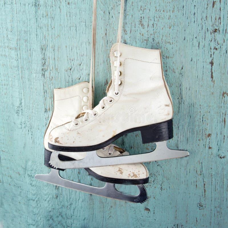 Patins de glace sur le fond en bois de vintage bleu photo libre de droits