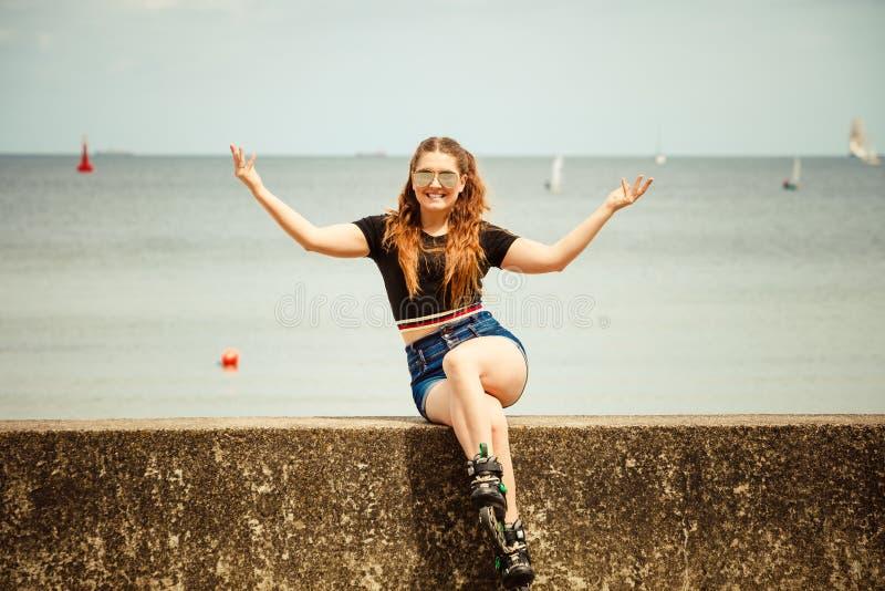 Patins de rolo vestindo da jovem mulher feliz fotografia de stock royalty free