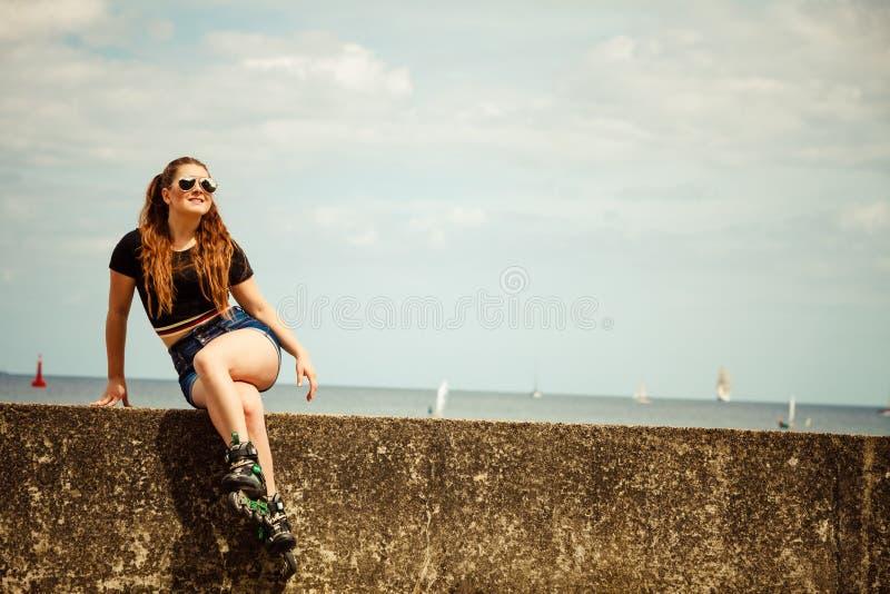 Patins de rolo vestindo da jovem mulher feliz imagem de stock royalty free