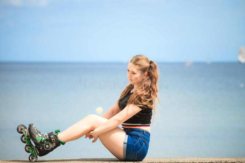 Patins de rolo vestindo da jovem mulher feliz fotos de stock royalty free