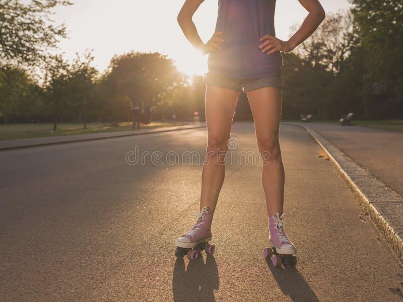 Patins de rolo vestindo da jovem mulher no parque no por do sol imagens de stock royalty free