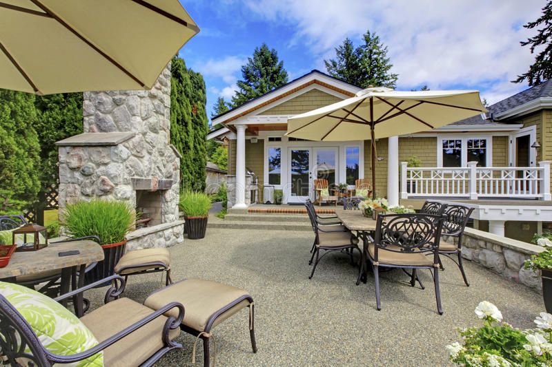 Patio area with stone fireplace and concrete floor. Patio table set with umbrella and deck chairs stock photography