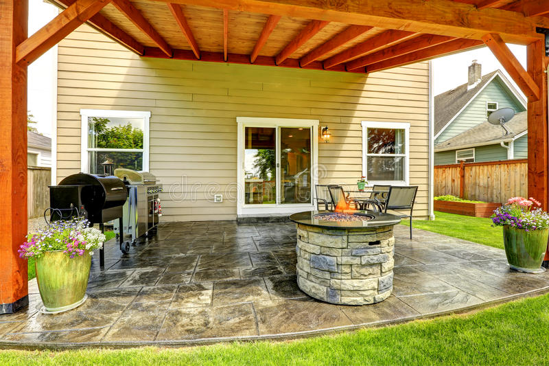 Patio area with tile floor and stone trimmed fire pit. Pergola with patio area. Tile floor decorated with flower pots. Stone trimmed fire pit, patio table set royalty free stock photography