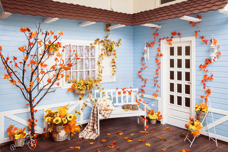 Patio in autumn season. Roof covered with tiles, blue wall. Patio in autumn season. Roof covered with tiles, blue wooden walls, white window with shutters, white stock photography