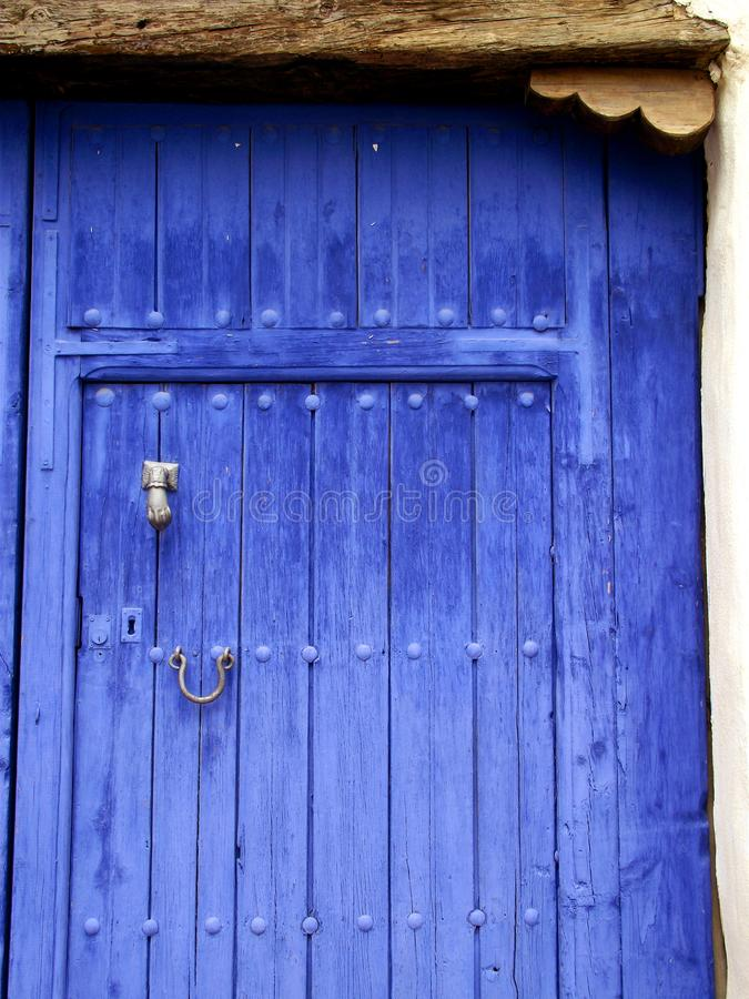 Patio blue wooden old door. Blue wooden old door to a patio in a village of La Mancha in Spain royalty free stock image