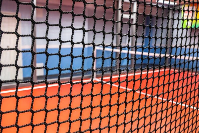 Patio borroso del tenis detrás de la red en el parque interior de la actividad fotos de archivo