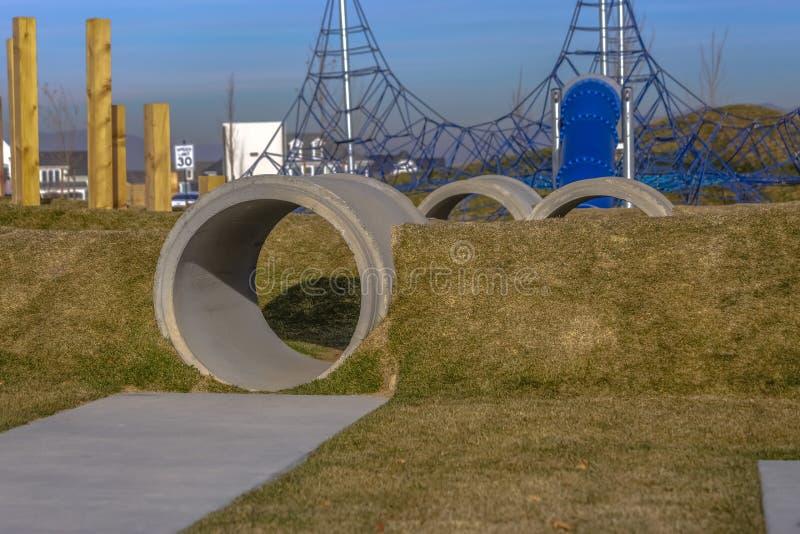 Patio con los túneles hechos de tubos concretos en los montones herbosos imágenes de archivo libres de regalías