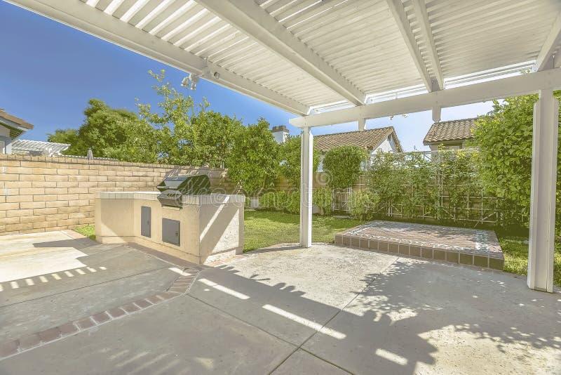 Patio concreto di una casa con la griglia del barbecue e la pergola di legno bianca fotografia stock