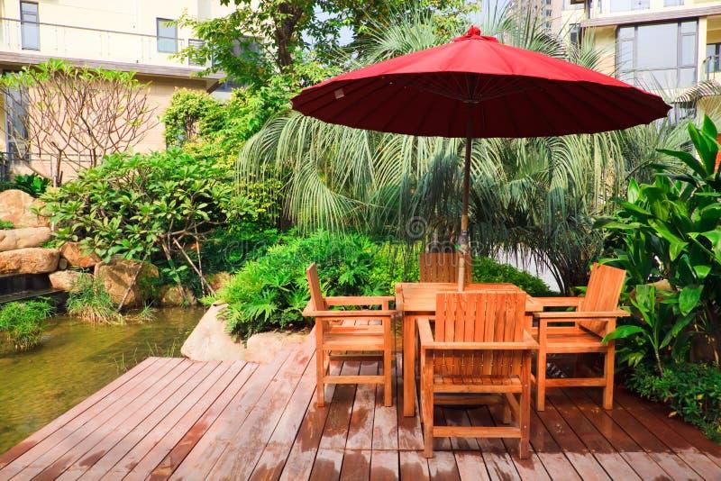 Patio d'été avec des tables et des présidences en bois photo stock