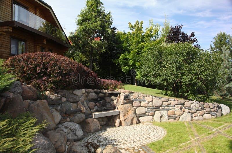 Patio de la pavimentadora del patio trasero con la charca en jardín Descripción que ajardina del patio de la pavimentadora del pa imagen de archivo