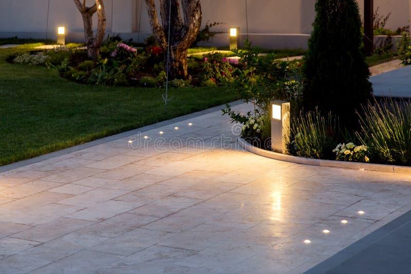 Patio de mármol de la teja en el patio trasero de macizos de flores y del césped con la linterna de tierra fotos de archivo libres de regalías