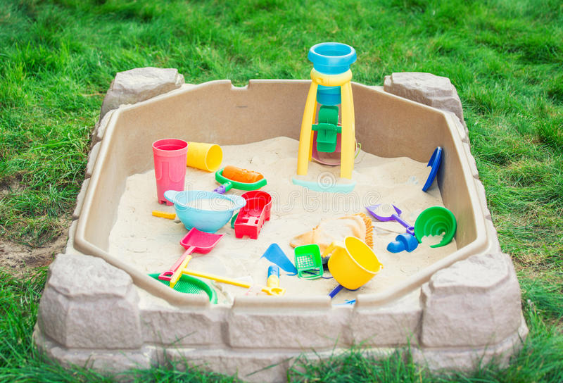 Patio del niño con la salvadera y juguetes en un patio trasero fotografía de archivo libre de regalías