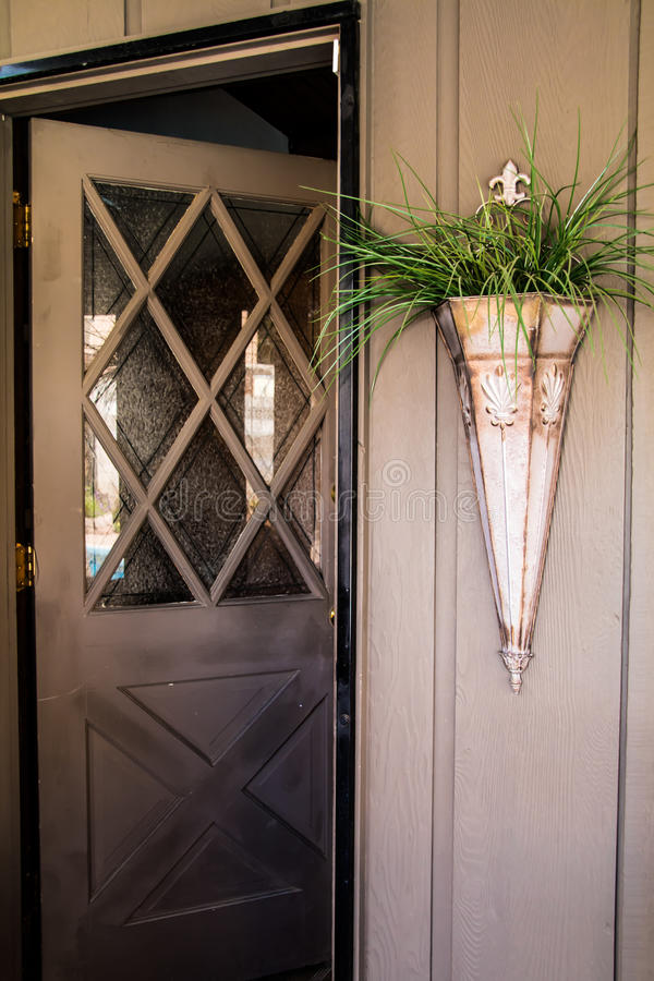 Patio door with a glass window. The patio entryway has a Brown cris-cross wood crossing the glass and the wood paneled wall beside the door is set off by a stock photo