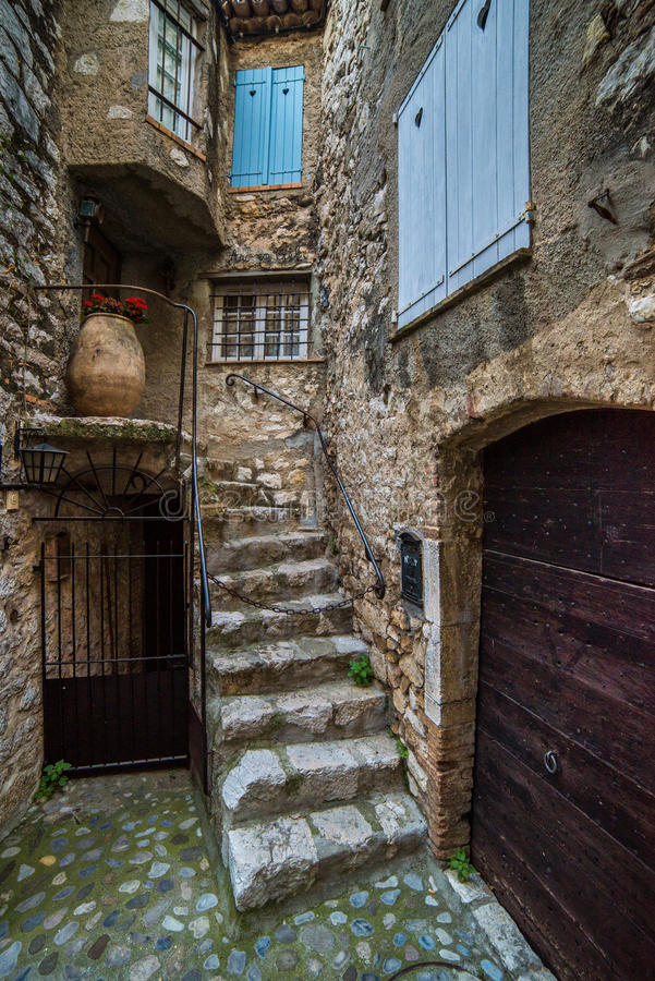 Patio with door, stairs and windows. SAINT PAUL DE VENCE , FRANCE - MAY, 2015: Wide-angle lens vertical shot of patio with door, stairs and windows in the stock photography