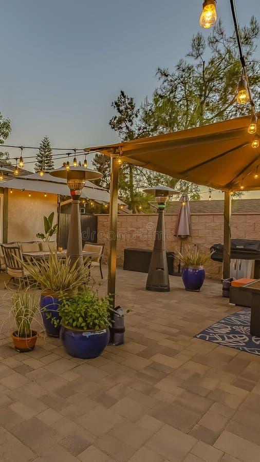 Patio en pierre confortable vertical avec de la ficelle des lumières au-dessus d'une allocation des places et d'une salle à mange photo libre de droits